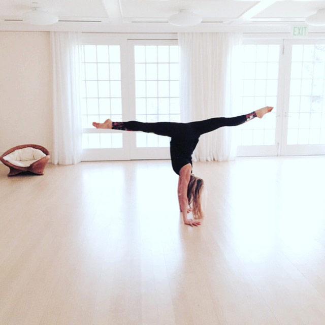 View larger photo of yogi Goldie Oren doing split handstand