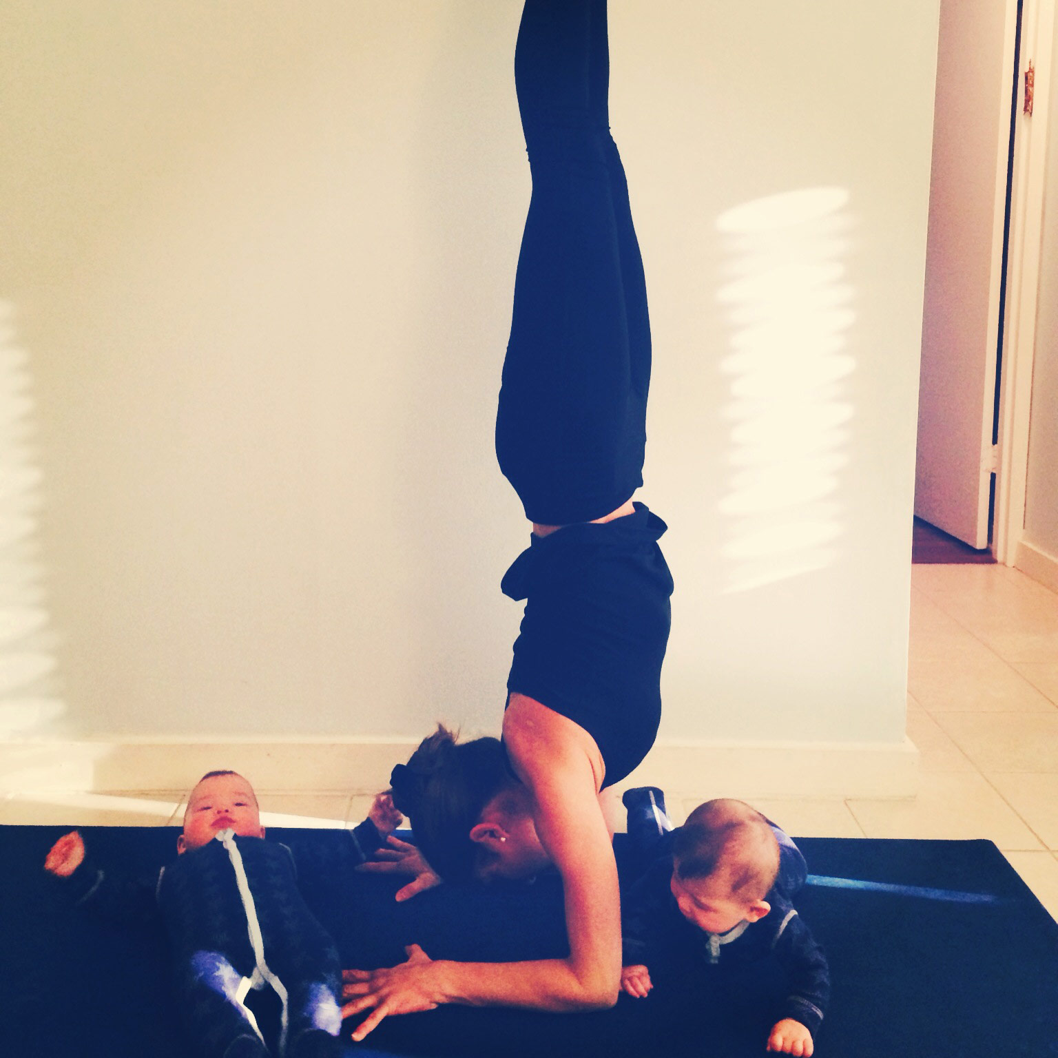 goldie oren doing yoga handstand with infants